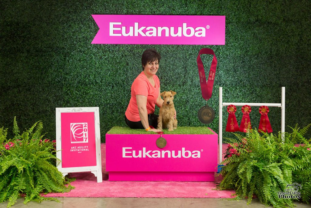 Lori Napoli sits on a podium with a dog under a banner that says Eukanuba.
